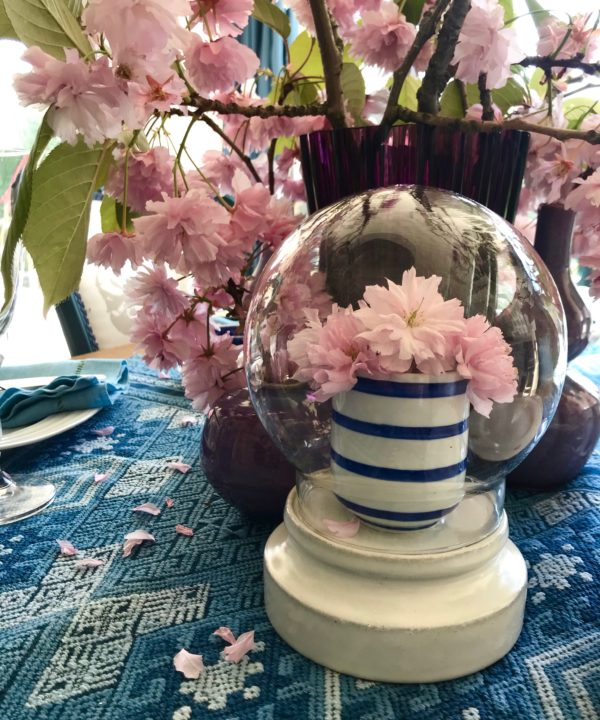 Display domes hand-crafted in Thailand, on a table with pink blossom blooms.