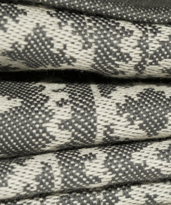 Close up detail showing the weave of a subtly patterned grey linen tablecloth.