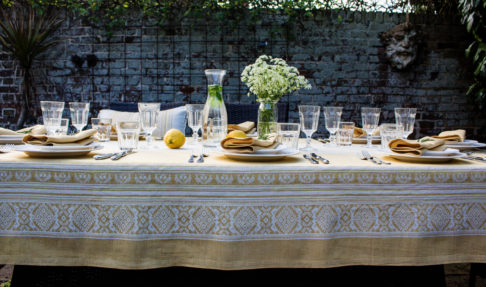 Yellow linen tablecloth with subtle motifs that reference Hungarian folk patterns. Draped over a table outside, set with glasses and tableware.
