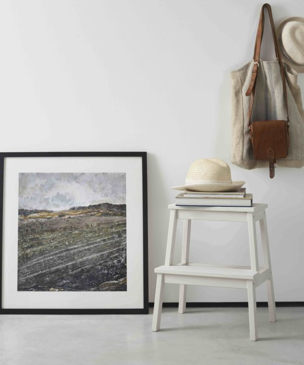 Northern Irish art print framed with a slim dark frame and leaned against a white wall next to a step stool with straw hats and bag on hook.