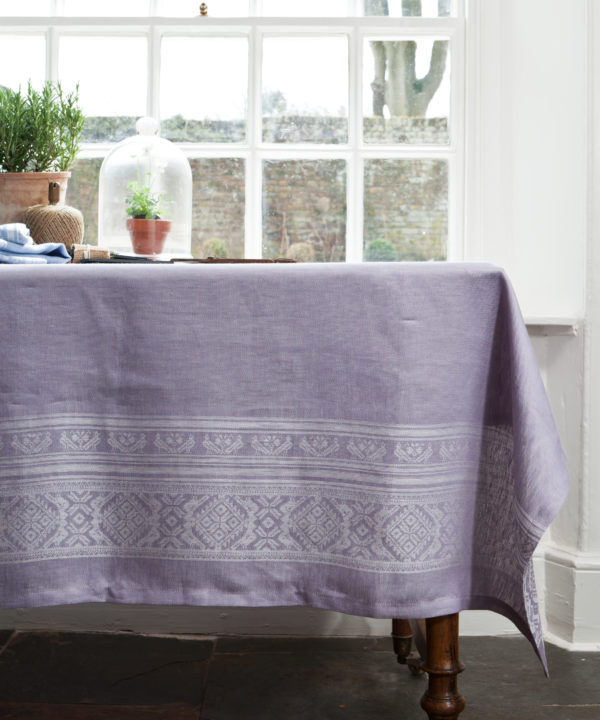 Purple tablecloth made from linen, with a Hungarian folk inspired jacquard weave, draped over a vintage mahogany dining table in front of a window.