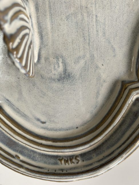 Detail of ceramicist's signature on a handmade, ceramic, butterfly wall art plaque.