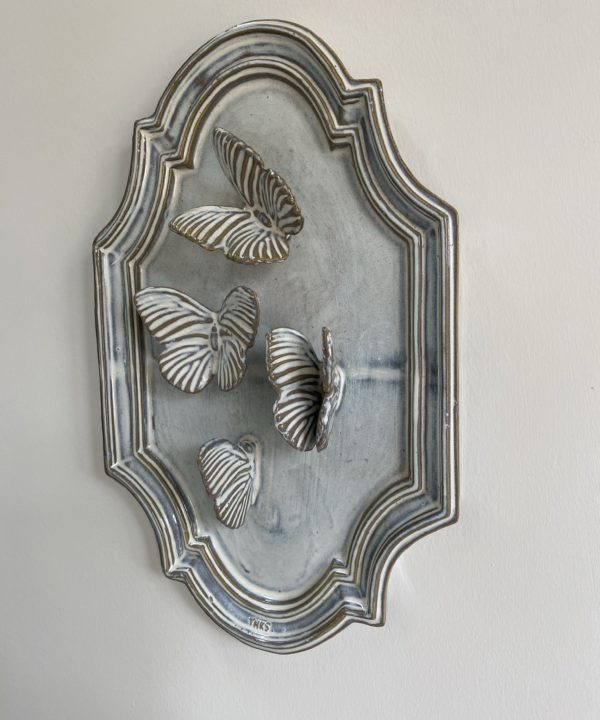 Side view of a handmade, ceramic, butterfly wall art plaque.