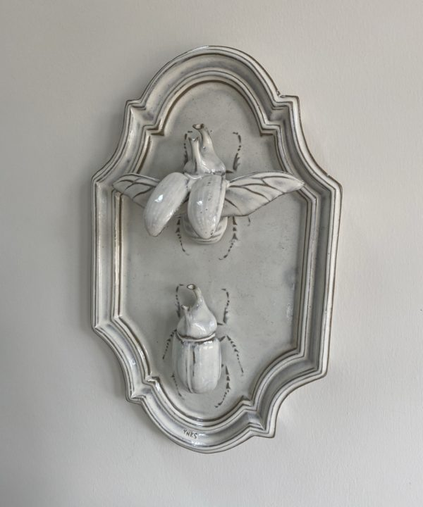 Side view of a ceramic wall art plaque depicting a rhino bug taking flight.
