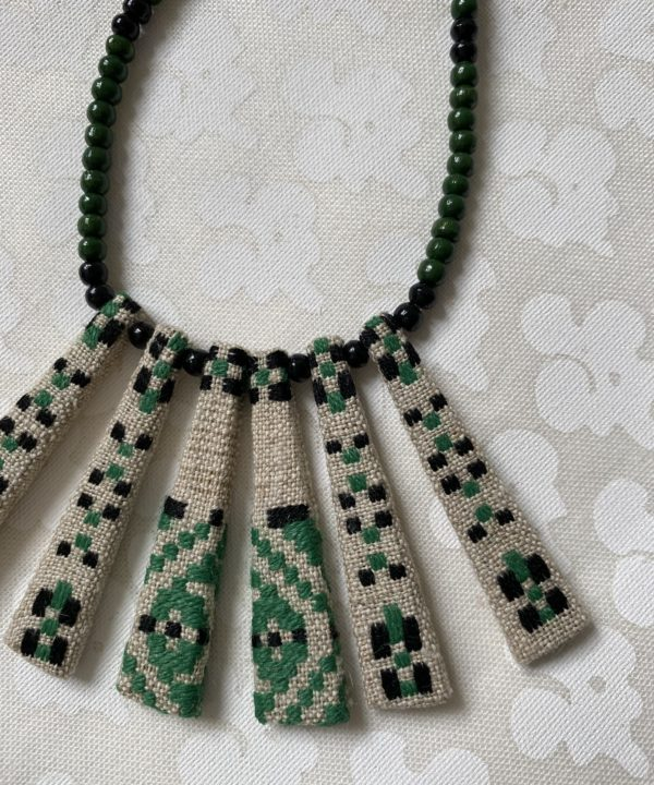 Bib necklace handmade from vintage Slovenian textile remnants, in black, white and green.