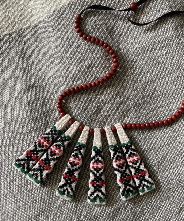 A folk pattern embroidered necklace in red, black and cream made from heritage Slovenian textiles and miniature beads.