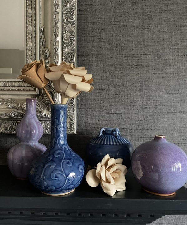 A selection of handmade Thai pottery displayed on a dark mantelpiece shelf against a silver mirror and grey textured wallpaper.
