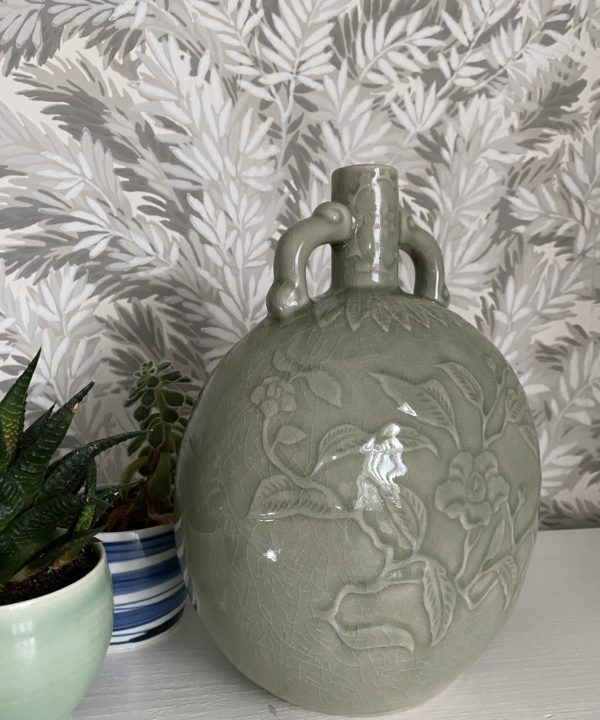 An elegant, celadon pottery pot with hand-decorated detailing photographed against a Cole & Son wallpaper depicting yew tree foliage in soft grey-greens.