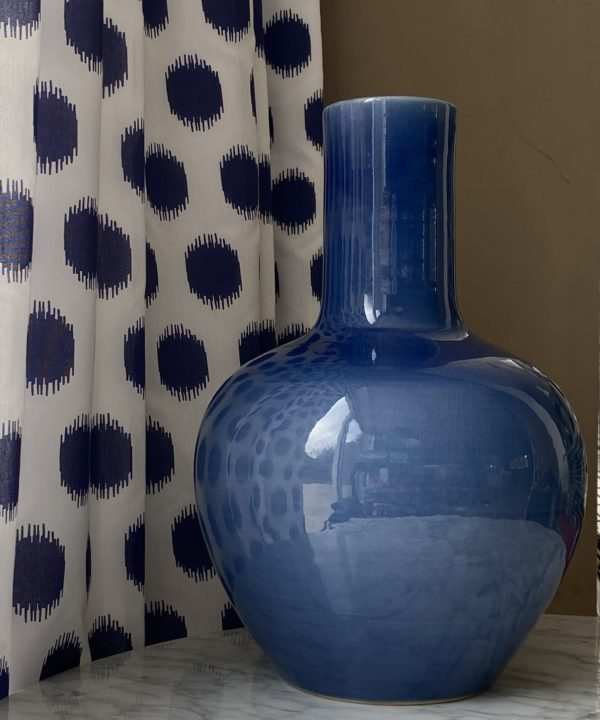 A decorative blue pot, largescale, against blue polka dot curtain fabric.