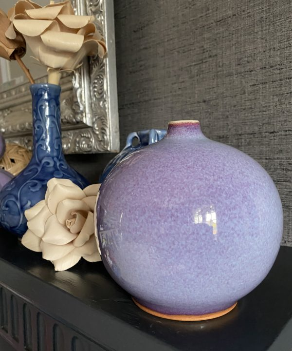 Handmade ceramic pot from Thailand in a purple Kinyo glaze sat on a dark mantlepiece with grey wallpaper behind.