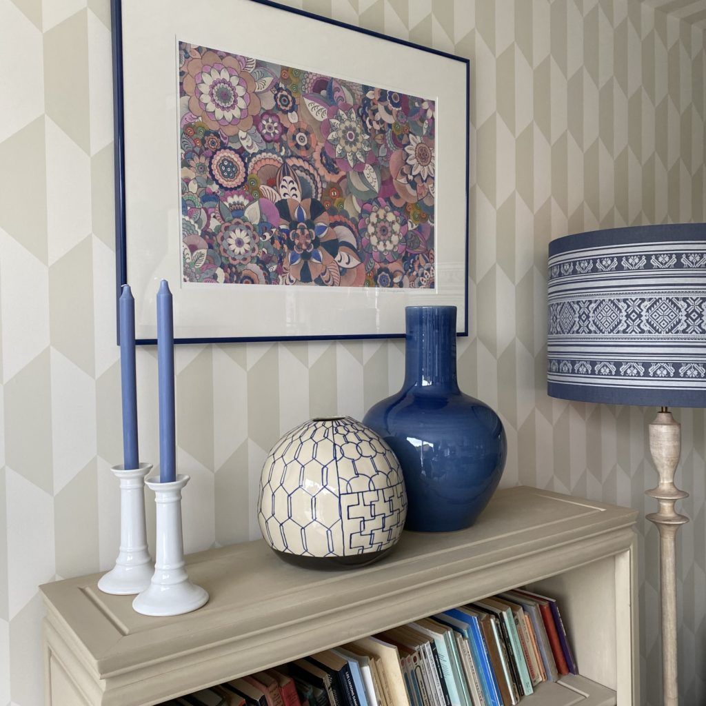 A still life display of Asian ceramics on a beige bookshelf with candlesticks and a pink floral Japanese artwork on the wall.