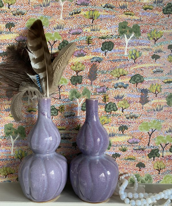 Purple ceramic pot, handmade in Thailand, double-gourd-shaped and shown holding feathers against a pretty, pastel, Aboriginal art wallpaper.