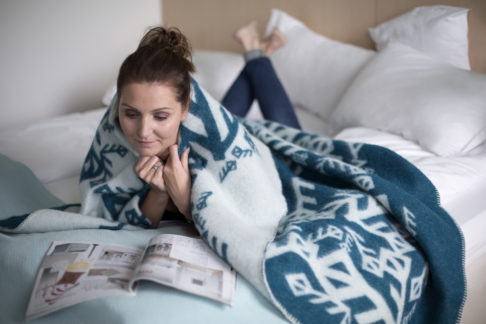 A lady snuggled up with the Nordic love blanket depicting ancient Norse bind runes meaning love.
