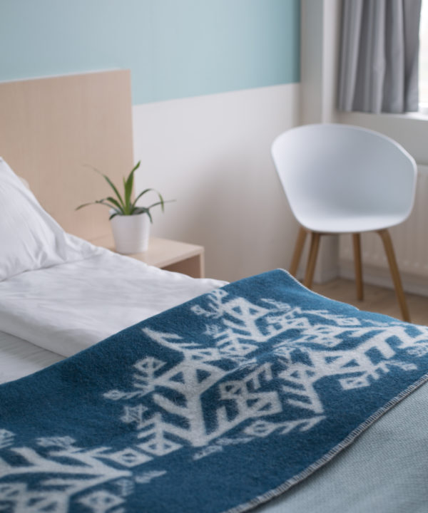 Folded teal blanket throw depicting Nordic bind runes symbolising love, on a bed.