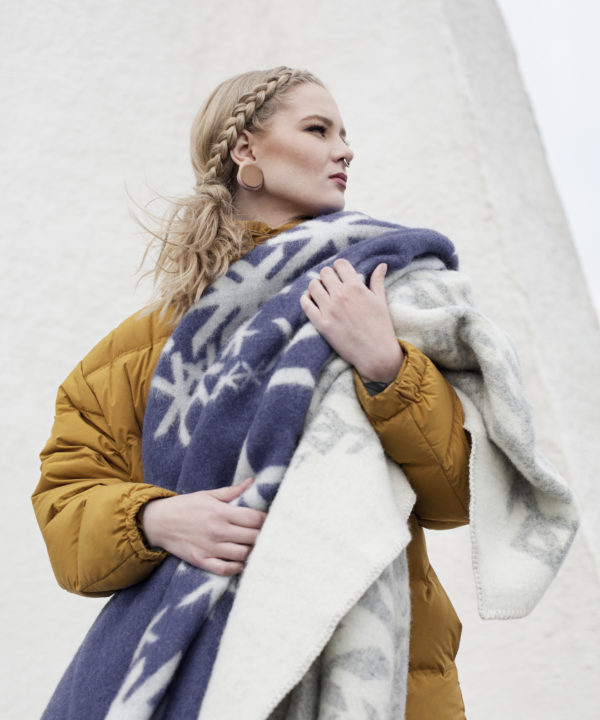 A navy blue blanket throw with ancient Norse symbolism bind runes design, held by a model.