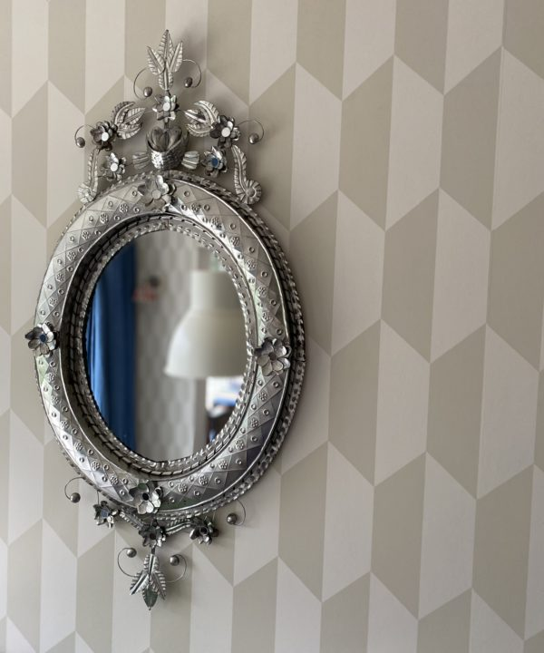 A Mexican tin art mirror hung against subtle, geometric modern wallpaper.