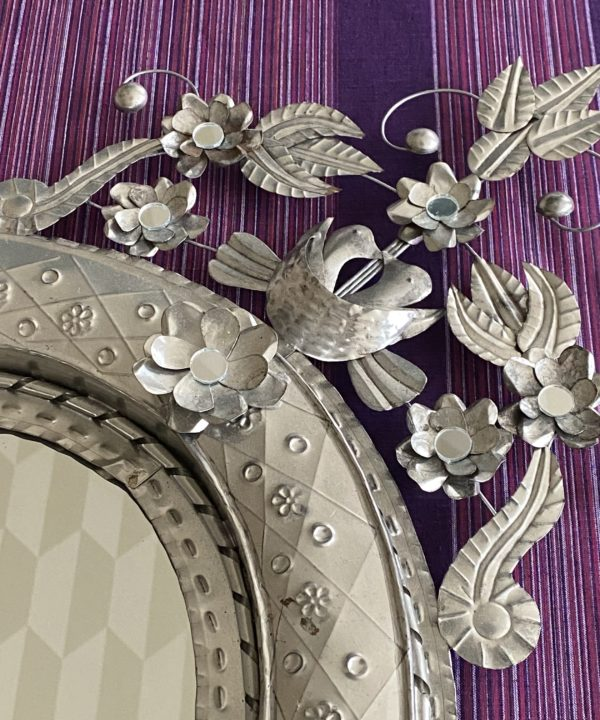 A decorative Mexican mirror against a purple striped backdrop.