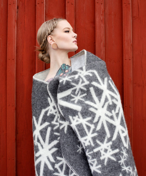 Grey blanket throw with Nordic bindrunes on a model against a red, wooden panelled shed.