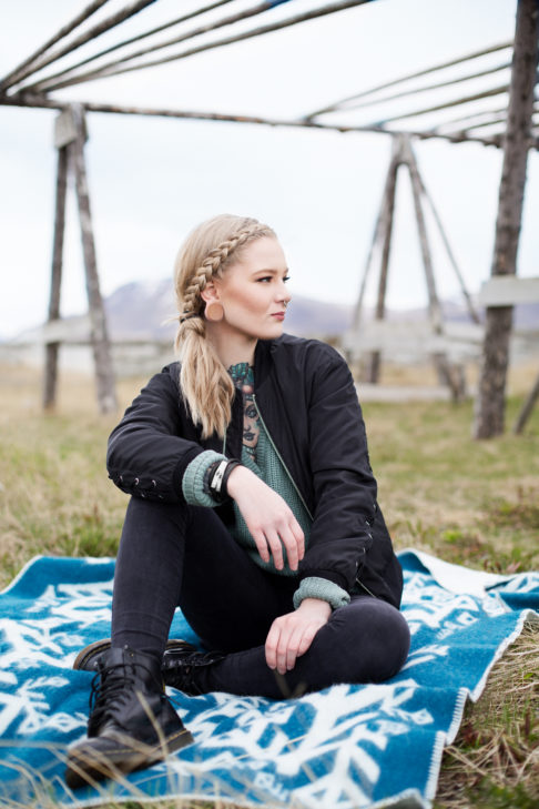 A model sitting on a teal blanket throw in the Icelandic countryside.