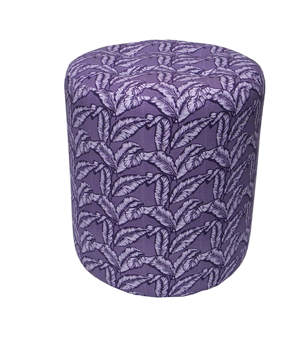 A purple upholstered dressing table stool with a tropical palm print.