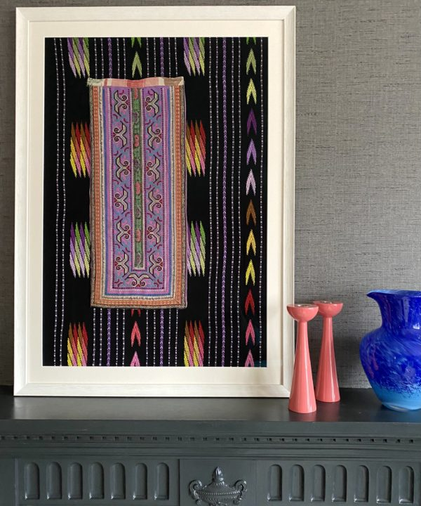 Unique wall art showcasing a hand-embroidered Thai textile framed against black and multi-coloured cloth.