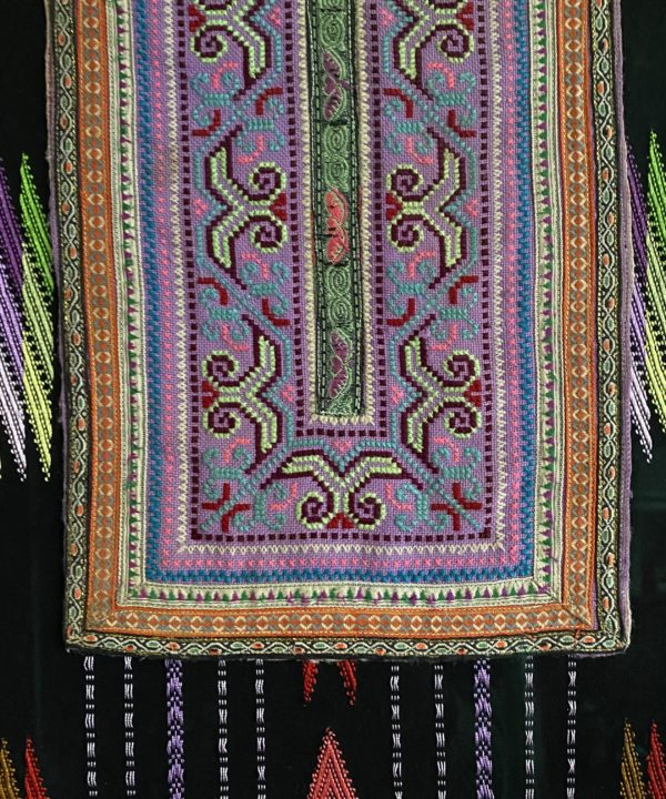 A unique wall art showcasing a vibrant, hand-embroidered Thai textile panel framed against black and rainbow-coloured woven cloth.