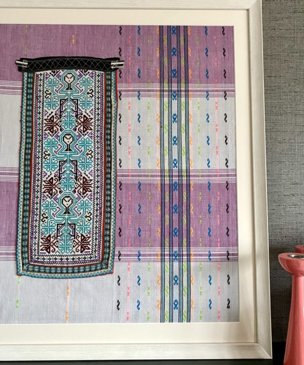 Fabric wall art from South East Asia framed and displayed on a ark mantelpiece with coral candlesticks in the foreground.