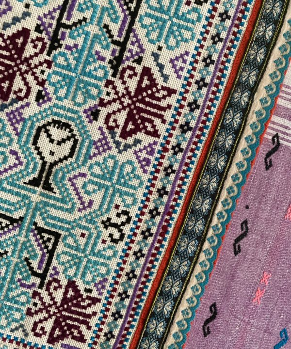 Close-up of Thai, hand-embroidered textile in blues and purples.