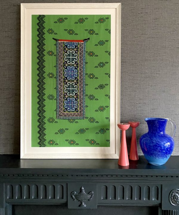 Thai textile wall art in blue, black and predominantly bright green framed and displayed on a grey mantlepiece.