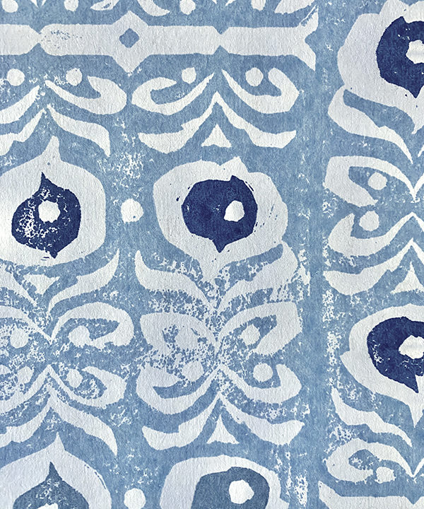 Detail of a hand-printed, light blue wallpaper with a Middle Eastern-inspired design.