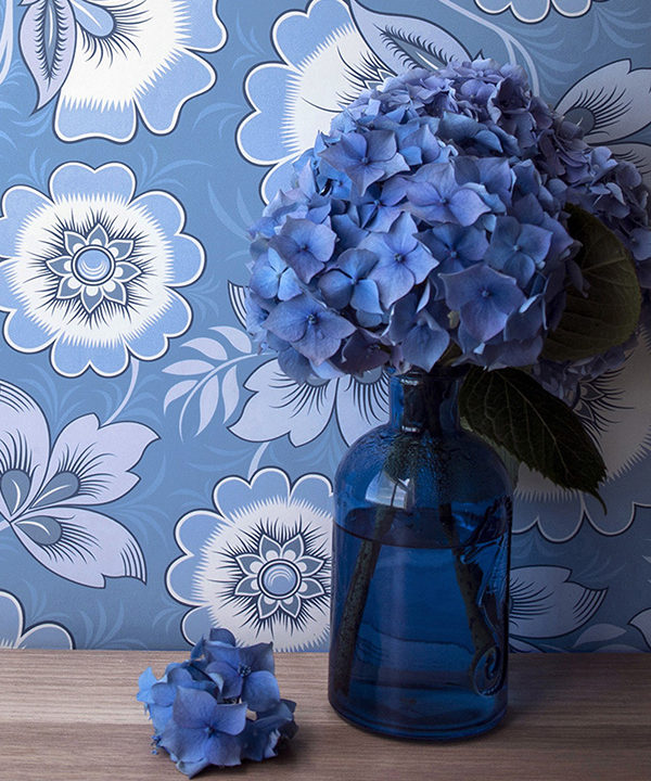 Floral folk art wallpaper in blue with hydrangeas in the foreground.