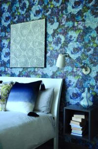 A modern, white ed against a blue floral Designers Guild wallpaper with anglepoise reading lamp and wall-hung bedside unit.