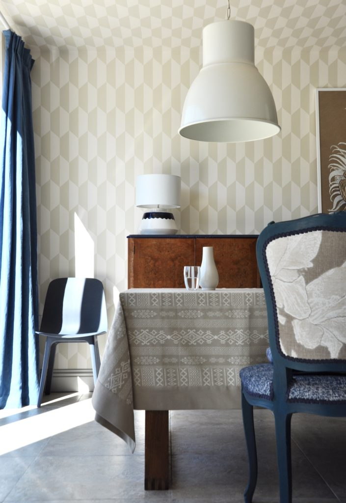 An elegant dining space in neutral hues and blue with large metal downlighters and geometric wallpaper.