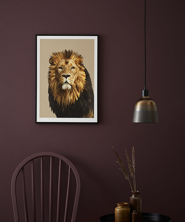 A majestic lion portrait is displayed against a deep aubergine painted wall.