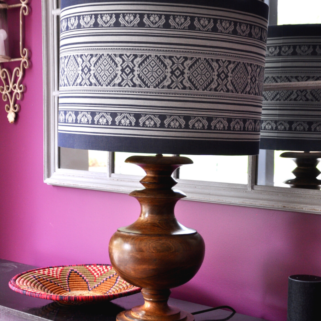 A Hungarian pattern drum lampshade on a wooden base against magenta pink walls.