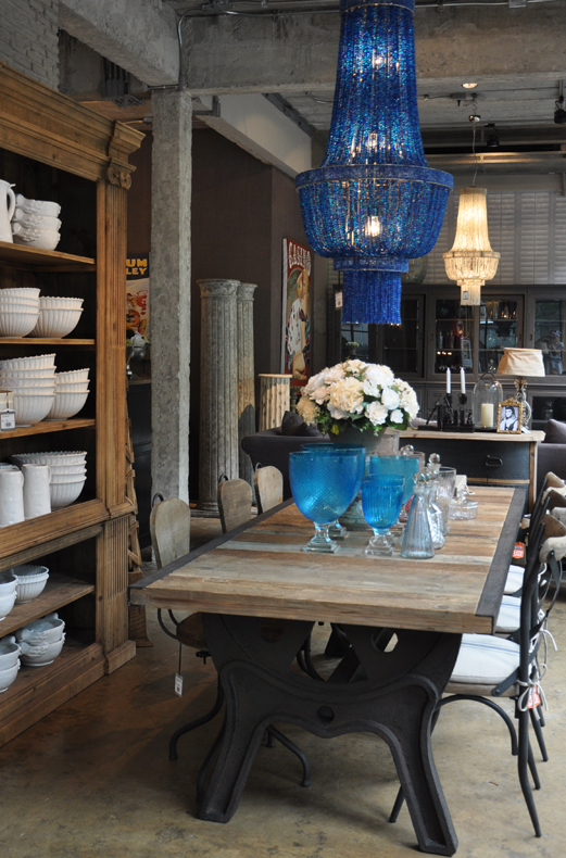 A stylish, vintage-inspired dining table in an urban loft space with a striking blue glass chandelier.