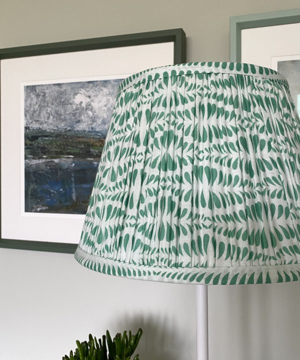 Green lampshades for table lamps are showcased here in a pretty mint colour way. The lampshade is block-printed and handmade in India and is shown here on an elegant sideboard.