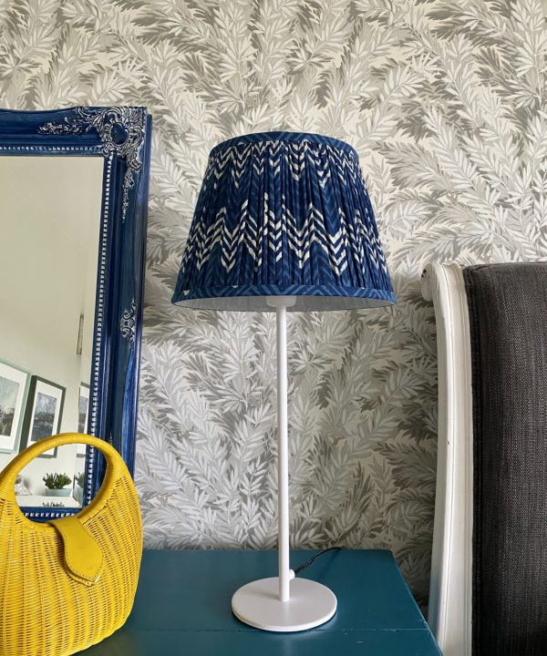 Indigo blue lampshades for table lamps displayed here on a simple, white candlestick lamp base on a teal sideboard with a blue decorative mirror and yellow wicker hand bag.