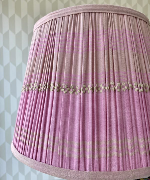Detail of a gathered cotton, baby pink lampshade.