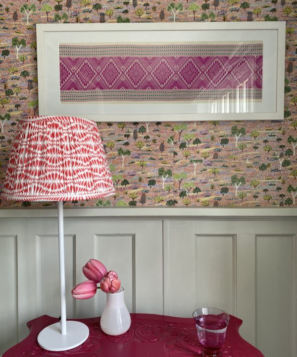 Pretty, cherry red lampshades for table lamps shown here on a pink, painted vintage table beside a four poster bed.